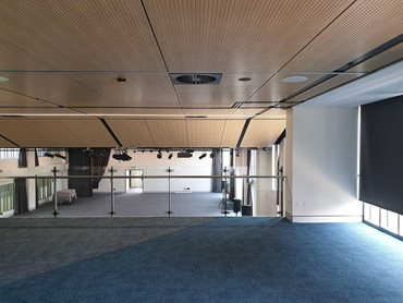 This ceiling addresses the acoustics across the wide area of the space. SUPAFINISH Black solid strips and returns are also featured.