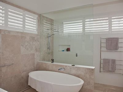 Bathroom interior with white plantation shutters