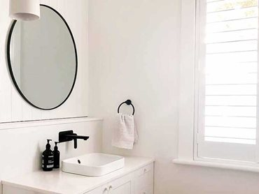 Caroma white basin with black tapware