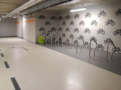 Detail of interior bike rack station with floor and wall wayfinding systems