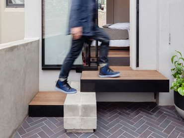 The materials palette includes mild steel, recycled timber floorboards, concrete, and herringbone brick facing tiles.