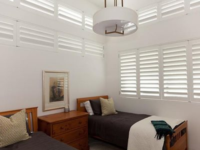 Bedroom interior with white plantation shutters