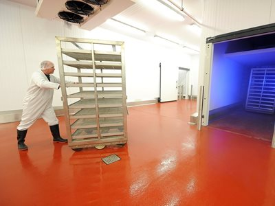Man pushing commercial food trolley into cool room