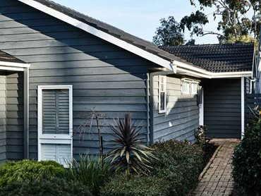 The exterior features freshly painted charcoal-coloured weatherboards