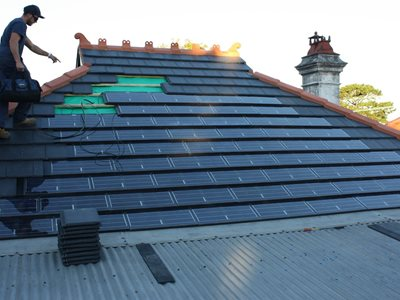 Progress image of solar tiles being assembled on roof
