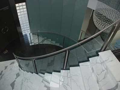 curved glass banister marble stairs