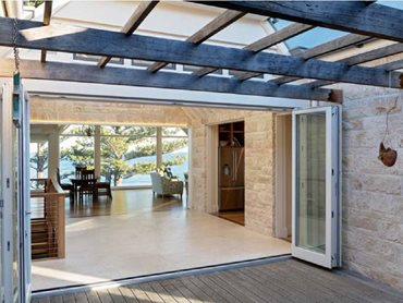A glazed atrium opens through bi-fold doors into a sheltered internal courtyard with decking