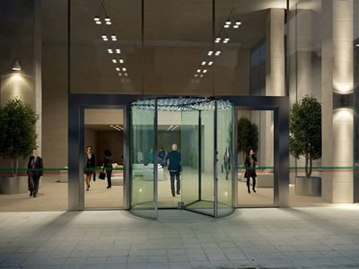 Rendered image of office building entrance with glass revolving door