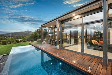 Full height glazing at the front of the home provides each room with views, and access to the expansive deck and the infinity lap pool