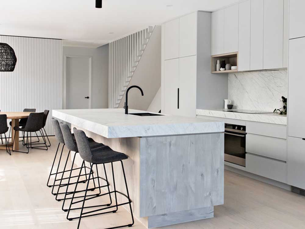 Mixing timber finishes and solid colours in kitchen design is a popular trend