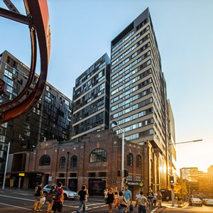Glass and metal surround Gehry's brick building in Sydney