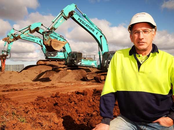 Micheal Bevilacqua with three of his Kobelco machines on a housing development site in Truganina in Melbourne's outer western suburbs